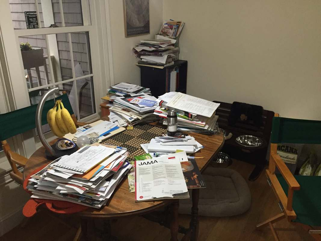 Before image of an unusable kitchen table that has become covered with piles of papers and magazines. Years of materials.