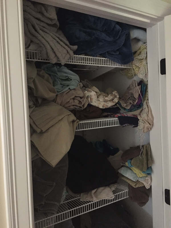 Before linen closet, messily stacked