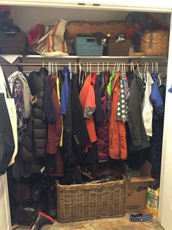 Before mudroom coat closet with packed jackets and shoes