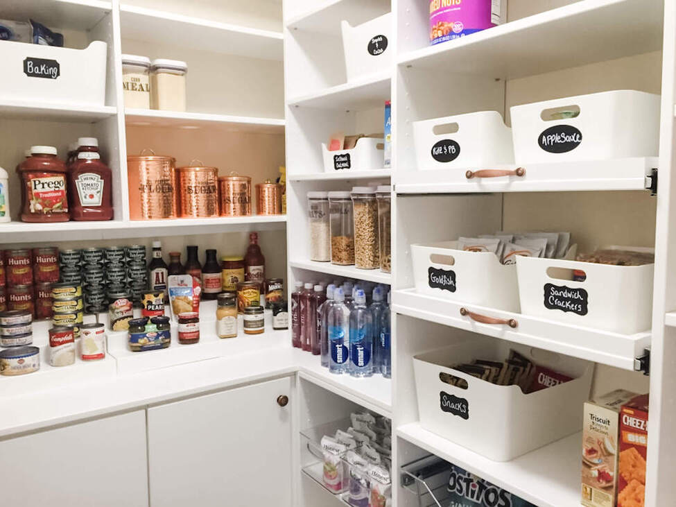 Bright white walk in pantry with white bins, chalkboard labels, shelves for cans in Portsmouth, NH home