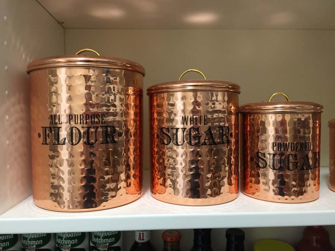 Copper canisters with stickers made to look like vinyl lettering- Flour and sugar.