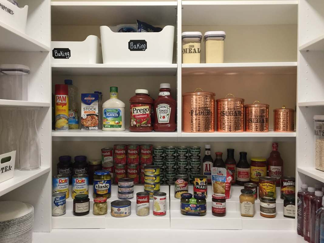 Bright white walk in pantry with white bins, chalkboard labels, shelves for cans, copper canisters for flour and more.
