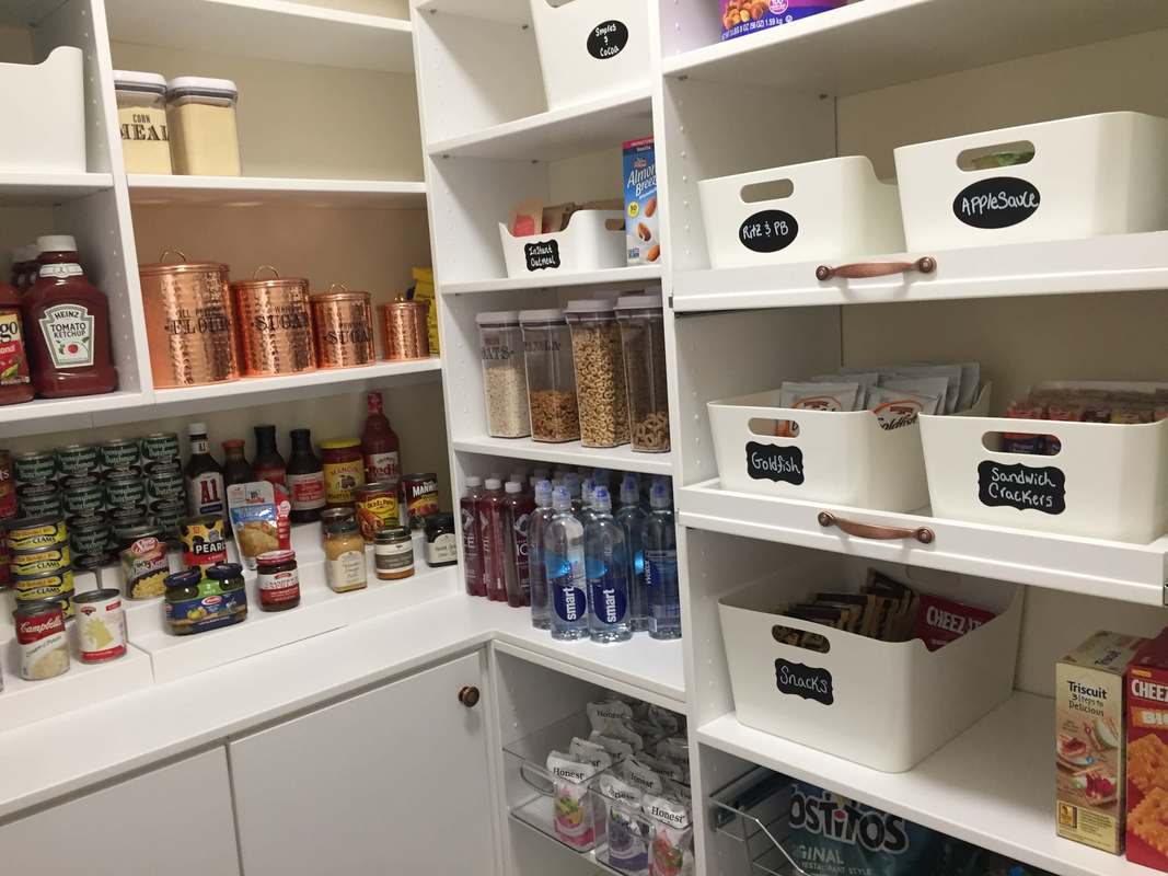 Bright white walk in pantry with white bins, chalkboard labels, shelves for cans.